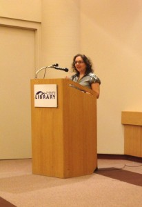 A photo of author A.M. Matte at a Toronto Public Library podium, reading a short story excerpt .