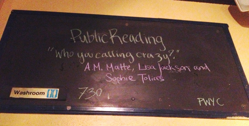 A chalkboald sign announcing the Who You Calling Crazy public reading