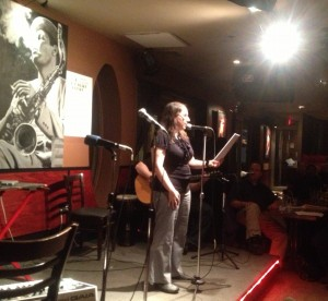 Under a spotlight and by a few microphones, A.M. Matte reads excerpts of her short story, Paper Dolls