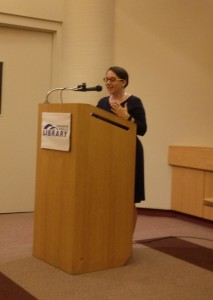 A.M. Matte reading an excerpt of Paper Dolls at the Toronto Public Library Main Reference Branch, at a wooden podium.