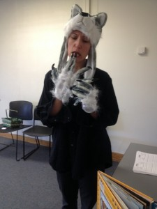 Improv actor C. Berthiaume in wolf hat and white, clawed gloves plays a wolf in Conte-moi ça interactive theatre for kids.